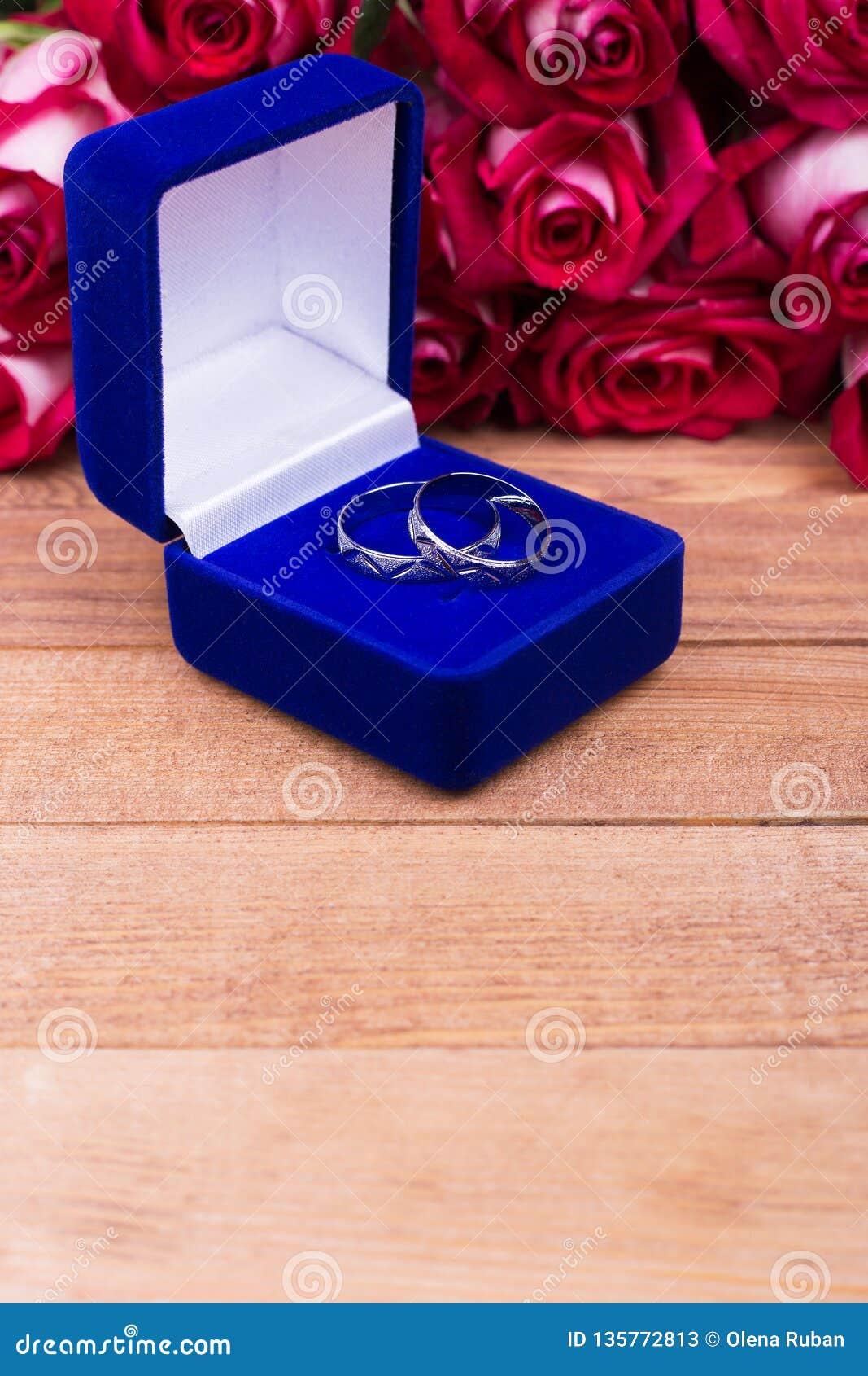 Caja azul con las joyas y las flores rojas