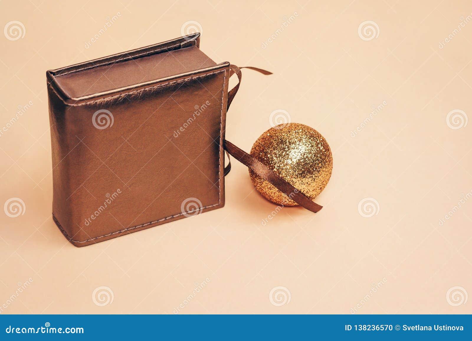Caja bronceada del estilo retro actual con un arco de seda solamente con la bola chispeante de la Navidad del oro en fondo en col