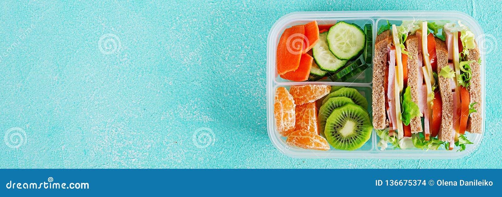 Caja de almuerzo escolar con el bocadillo, las verduras, agua, y las frutas en la tabla