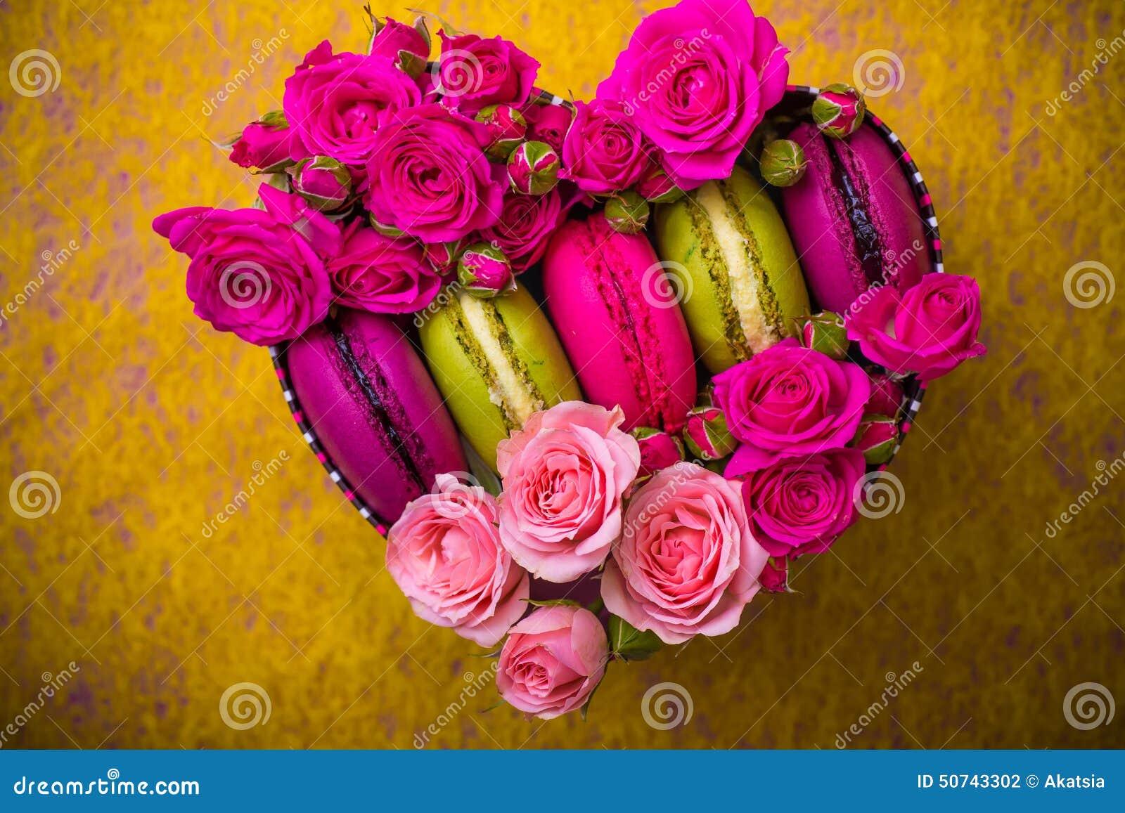 Caja de la forma del corazón con el fondo de los macarrones del color de la primavera del rosa de la baya con amor
