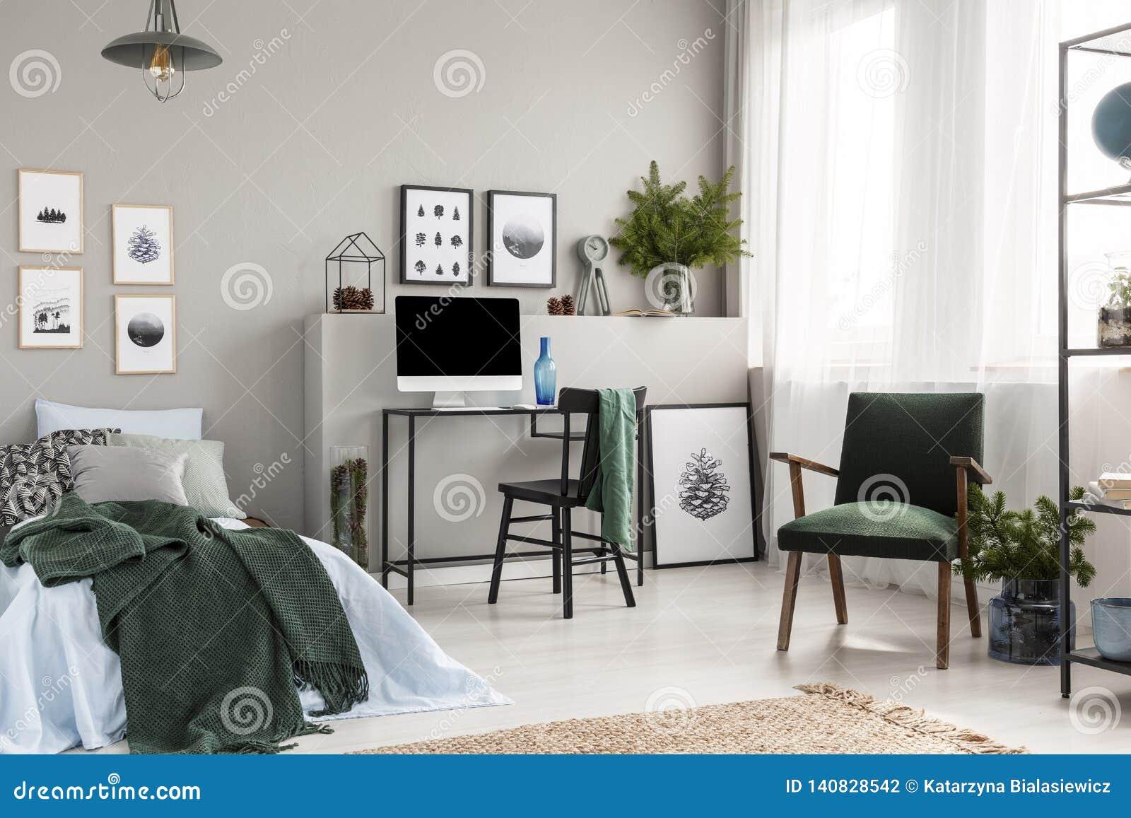 Caja de madera debajo de la sola cama del metal con las hojas azules y la manta verde en el sitio del niño de moda con espacio de