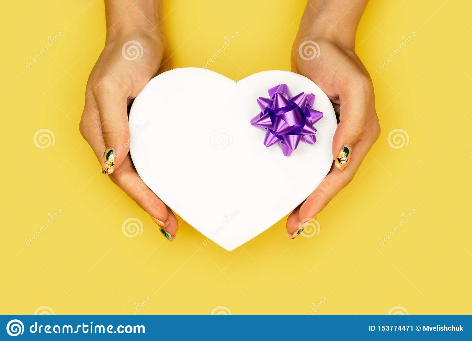 Caja de regalo blanca de la forma del corazón en manos de la mujer en fondo amarillo con el espacio de la copia