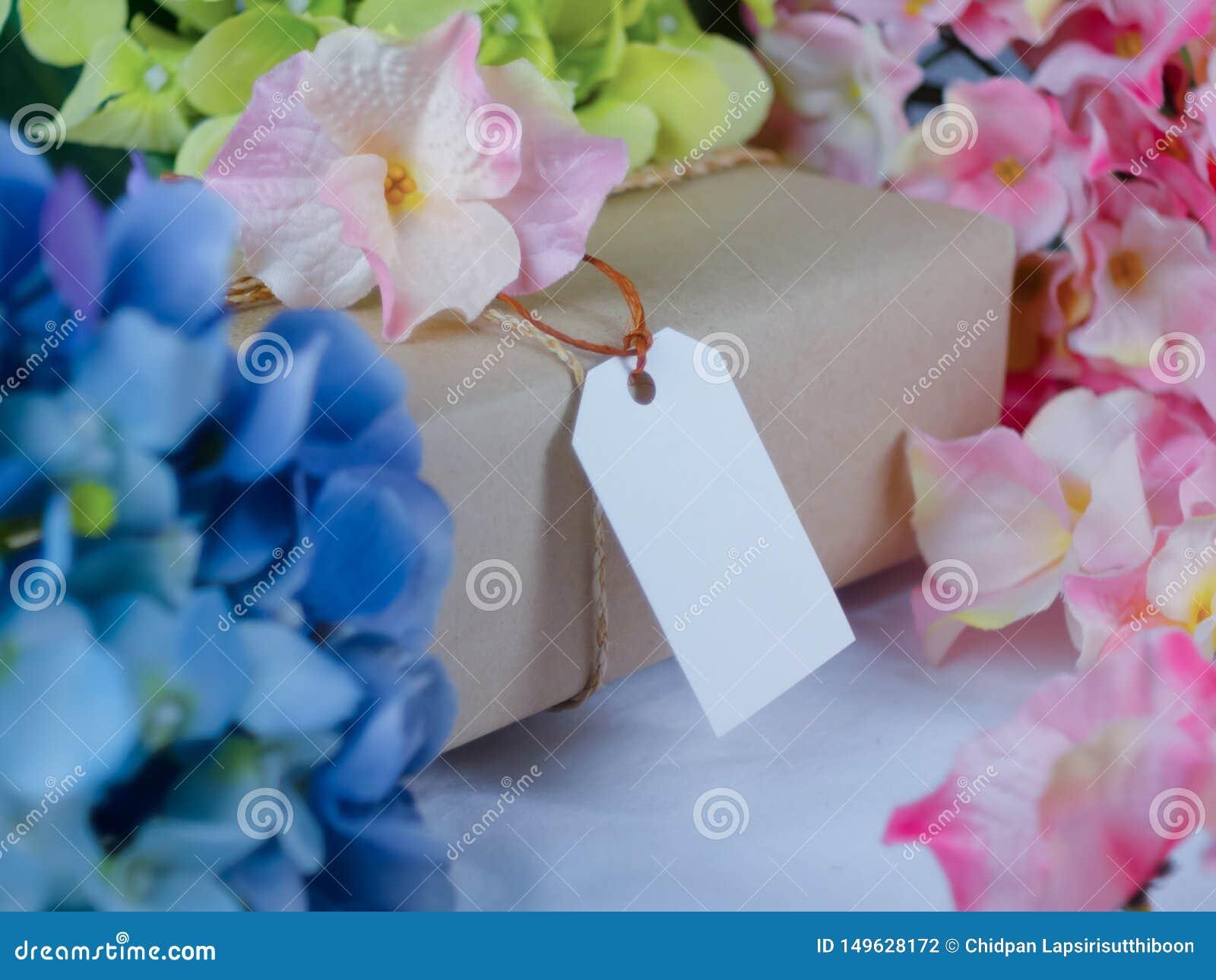 Caja de regalo de Brown con las etiquetas de papel en blanco y colocada en medio de las flores azules y rosadas