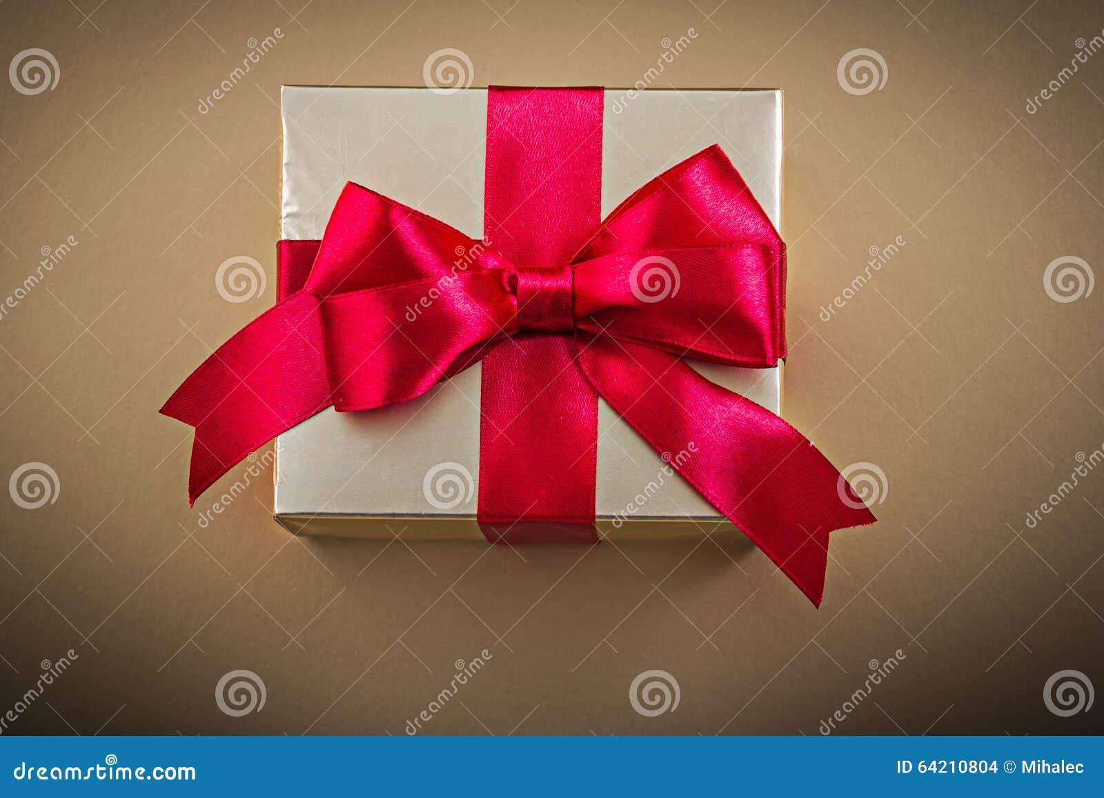 Caja de regalo con el arco atado en fondo de oro