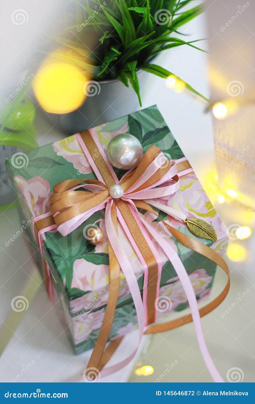 Caja de regalo con el arco de la cinta y la decoración de la perla