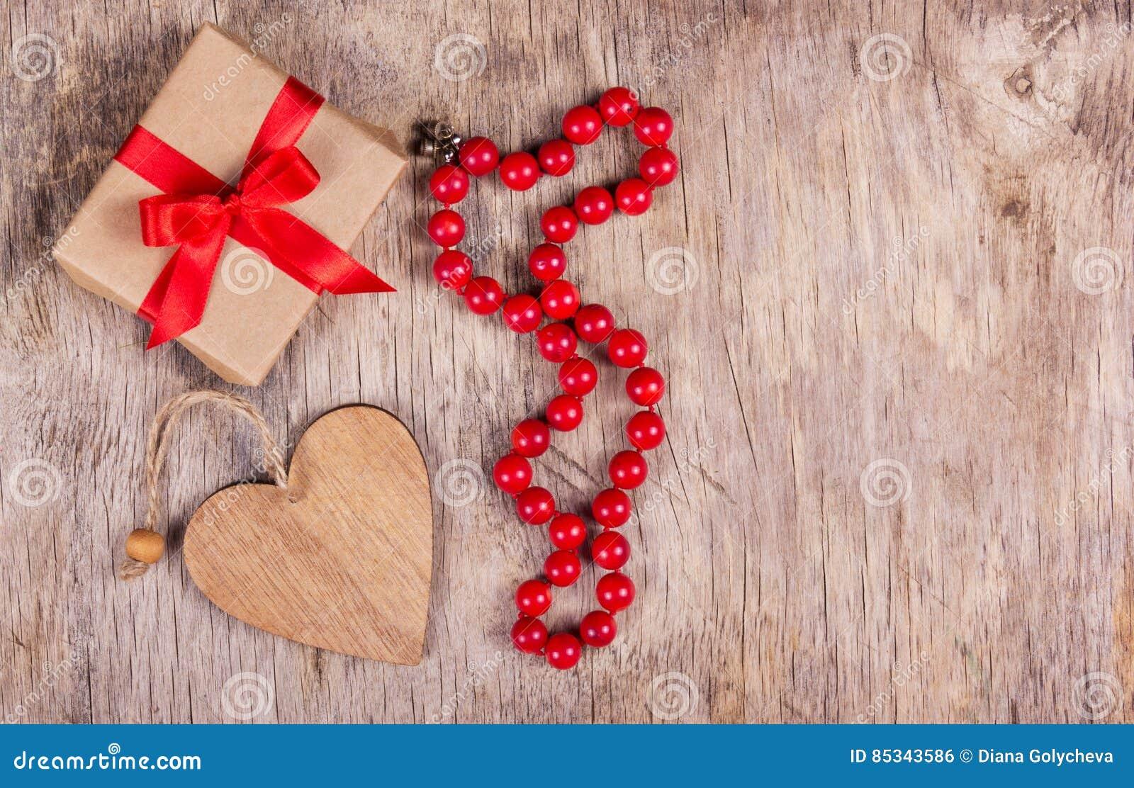 Caja de regalo con el arco rojo, la tarjeta del día de San Valentín y el collar coralino en el viejo fondo de madera St Día del `