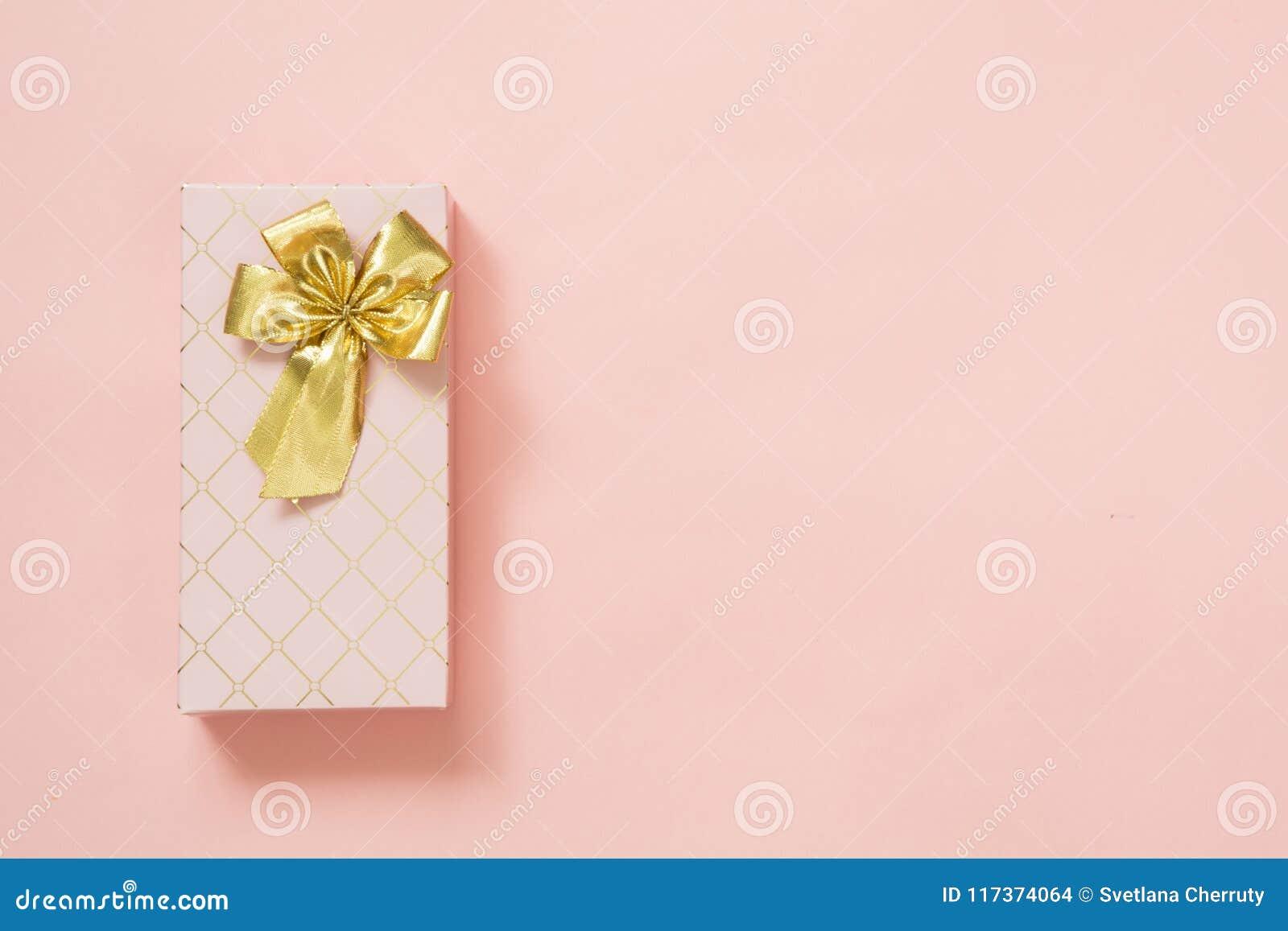 Caja de regalo femenina con la cinta de oro en rosa en colores pastel dinámico Cumpleaños Copie el espacio