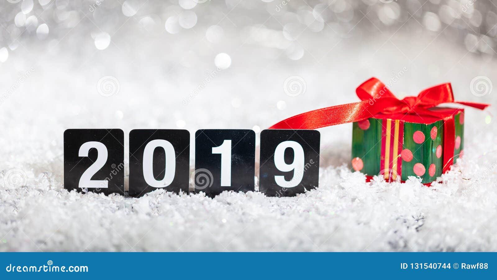 Caja de regalo de la Navidad y Año Nuevo 2019, en nieve, fondo abstracto de las luces del bokeh