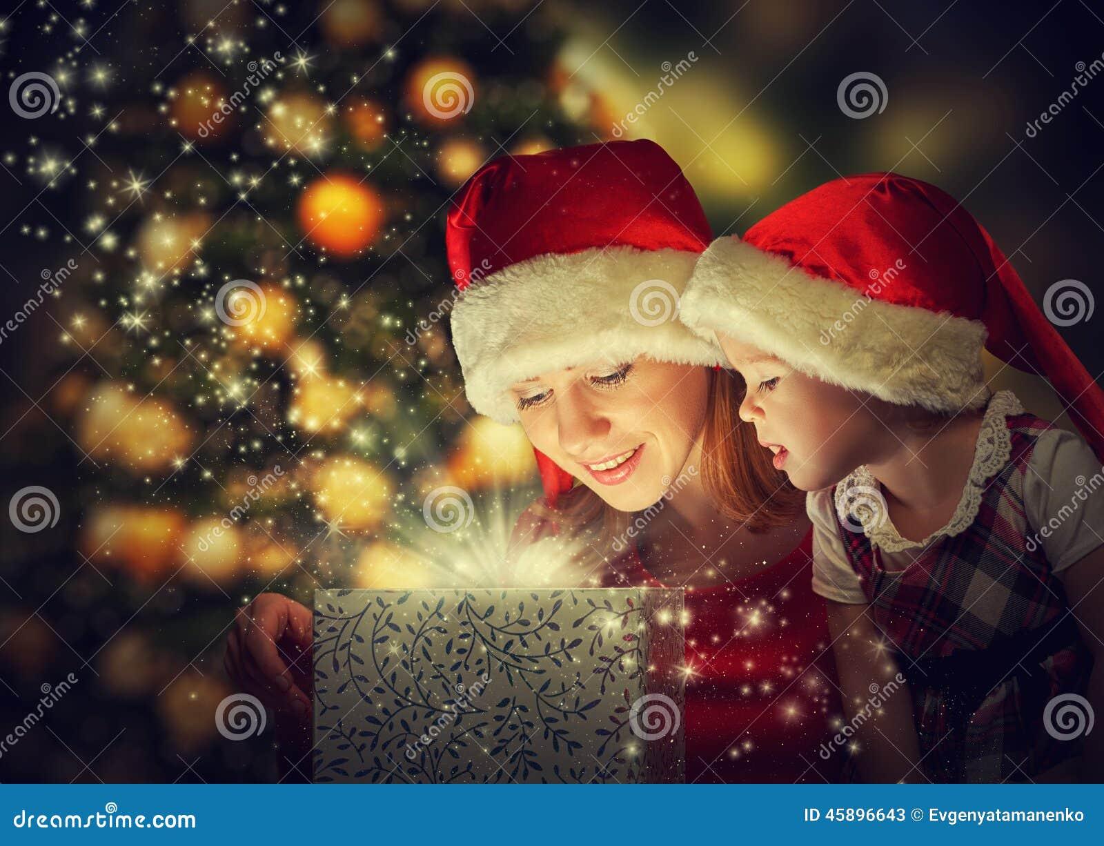 Caja de regalo mágica de la Navidad y un bebé feliz de la madre y de la hija de la familia