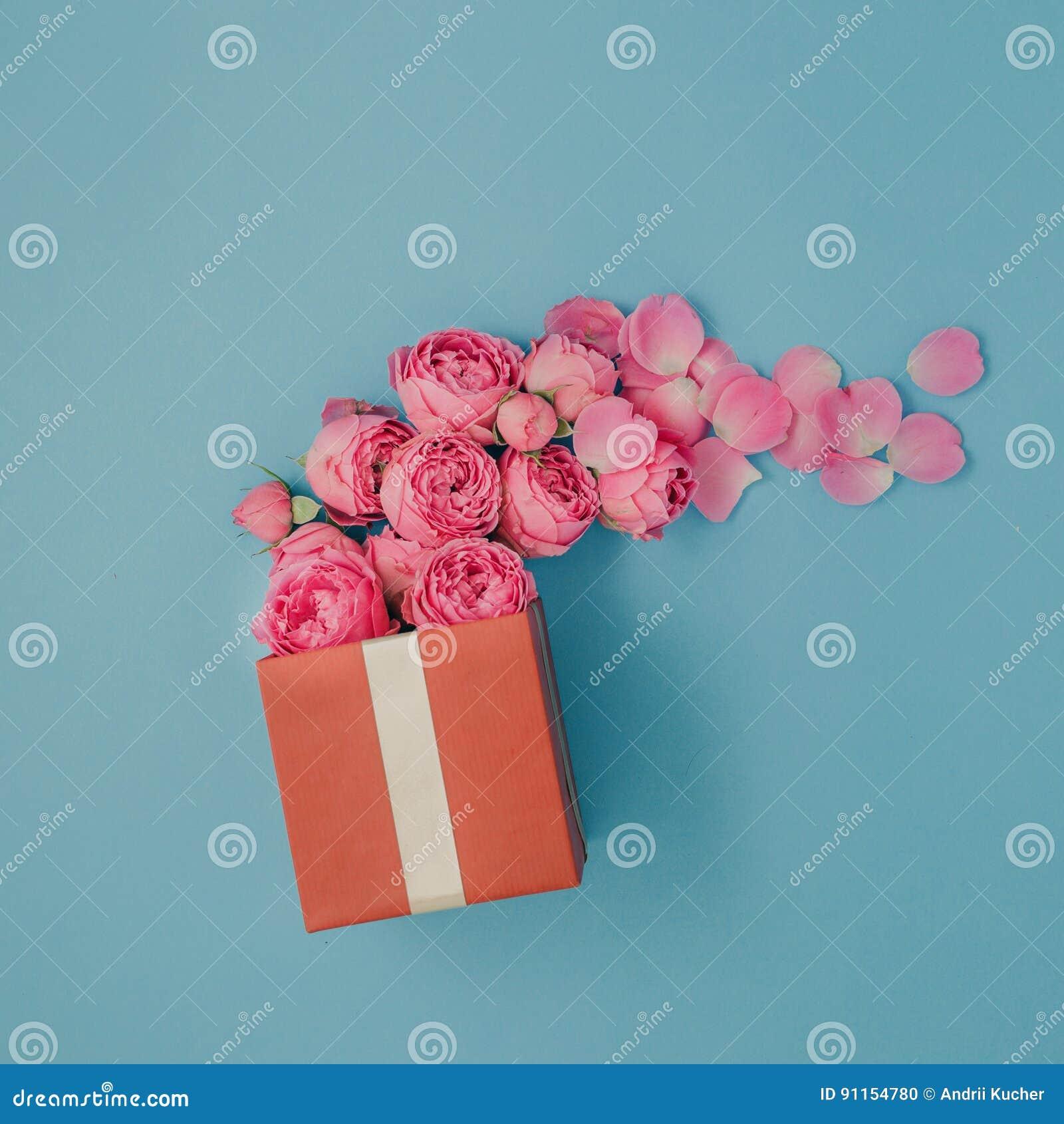 Caja de regalo roja llena de rosas rosadas en fondo azul