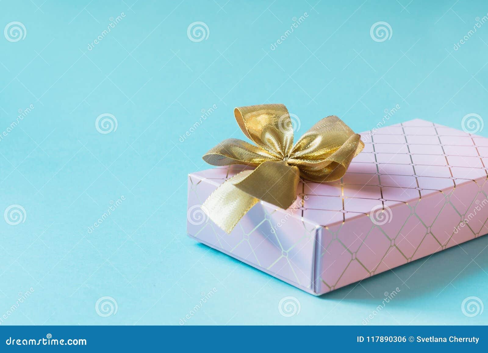Caja de regalo rosada femenina con la cinta de oro en rosa en colores pastel dinámico Cumpleaños Copie el espacio
