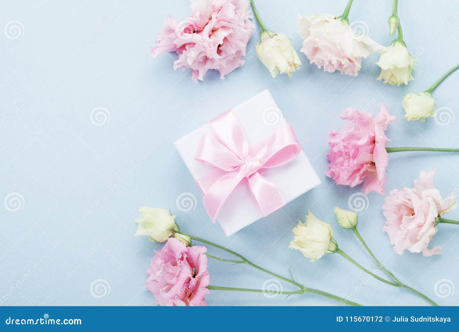Caja de regalo y flores en colores pastel para el día de madres en la opinión de sobremesa azul estilo plano de la endecha