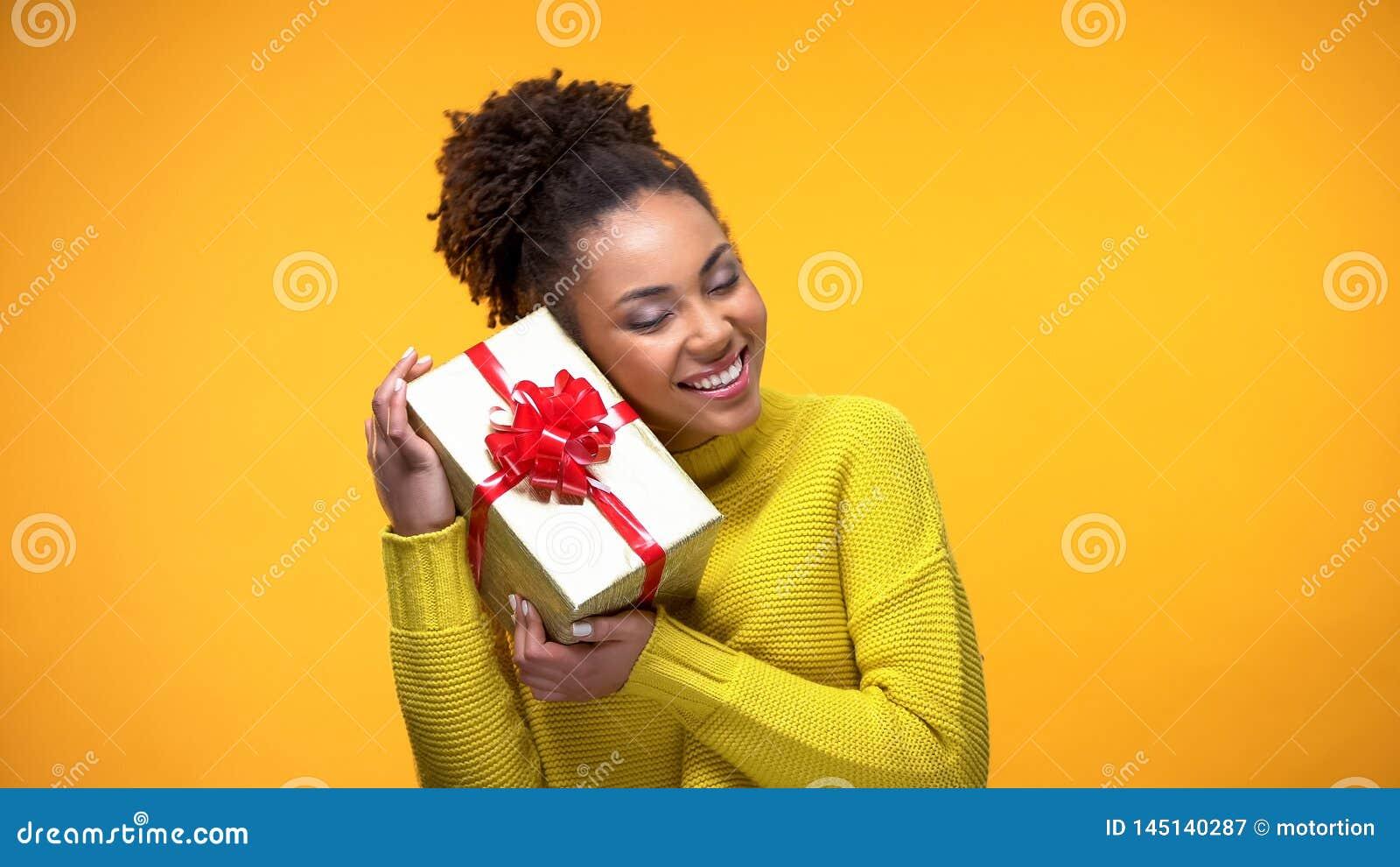 Caja que se sostiene femenina del africano feliz actual con el arco rojo, sorpresa del regalo de cumpleaños