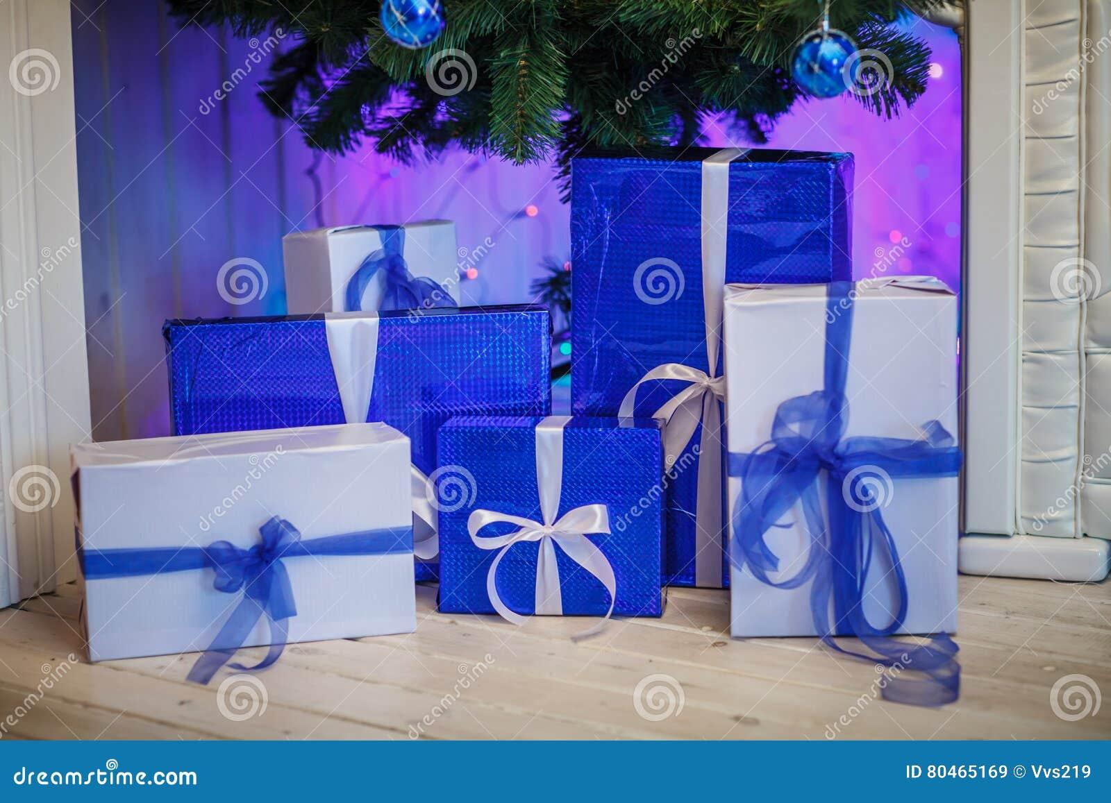 Cajas azules y blancas de la Navidad debajo del árbol Regalos del Año Nuevo