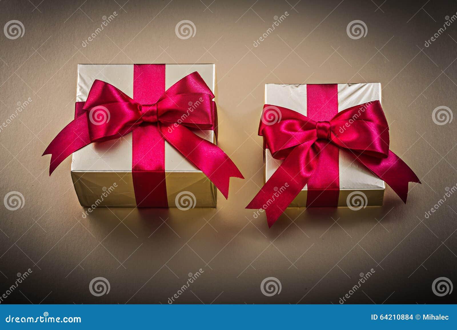 Cajas de regalo con las cintas atadas en superficie de oro
