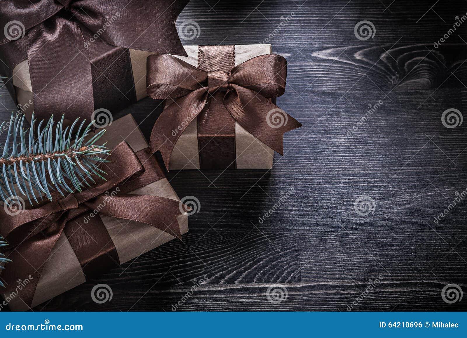Cajas de regalo de la Navidad de la rama del abeto en el tablero de madera
