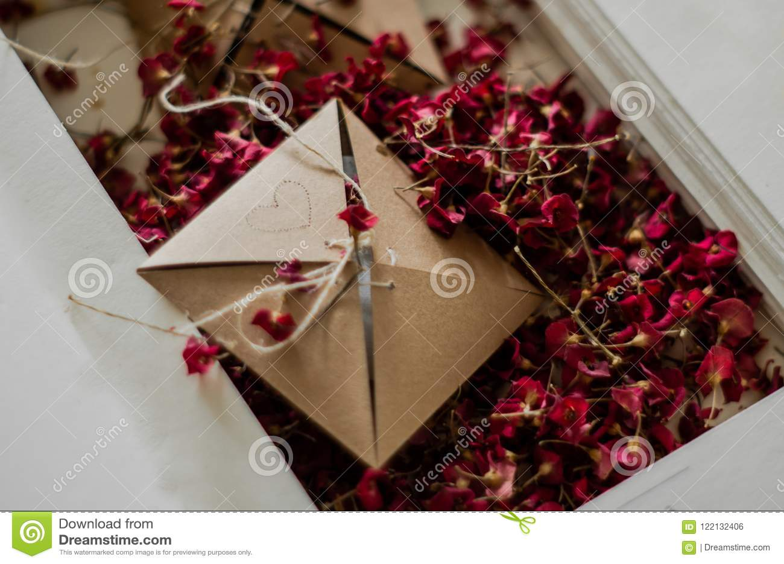 Cajas del vintage con las flores rojas secadas en una cama blanca Nostálgico del concepto y fondo del vintage de la conmemoración