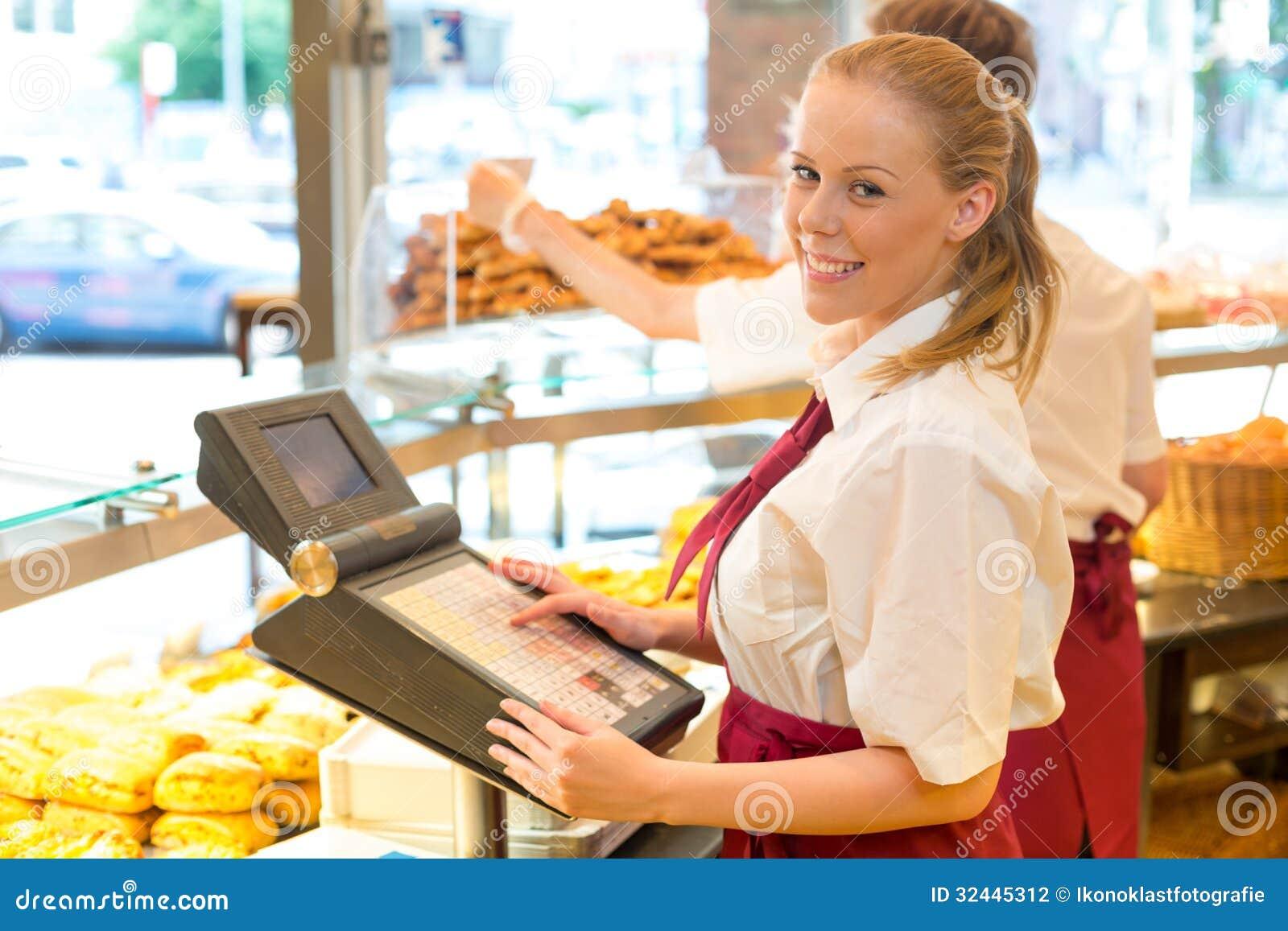 Cajero en la tienda del panadero que presenta con la caja registradora