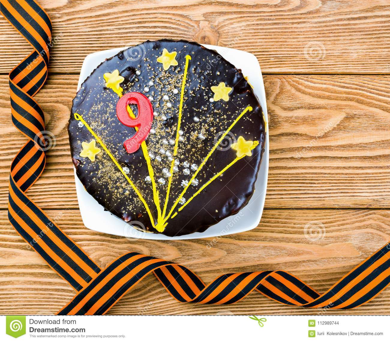 Cake on a plate and St. George ribbons on a wooden background in honor of May 9