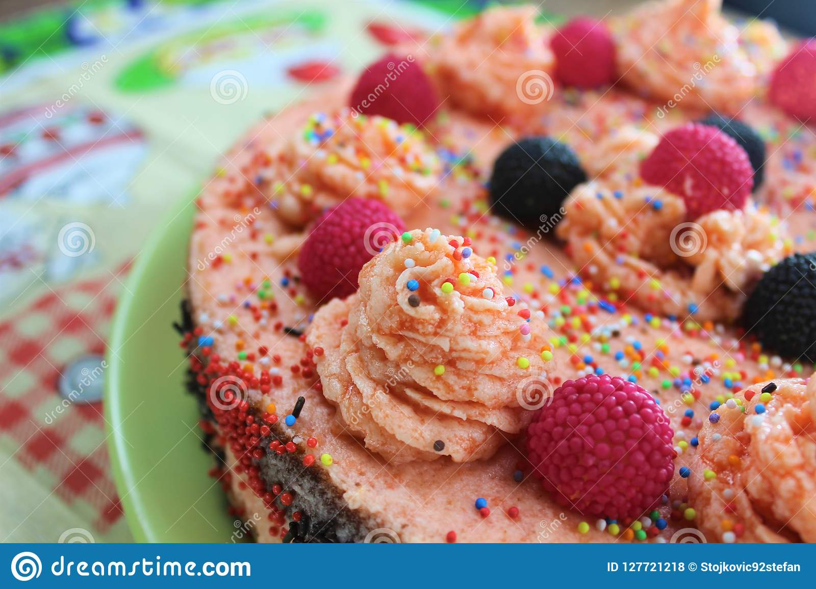 Cake with strawberries, blackberries and colorful sprinkles on the green plate and colorful strawberry