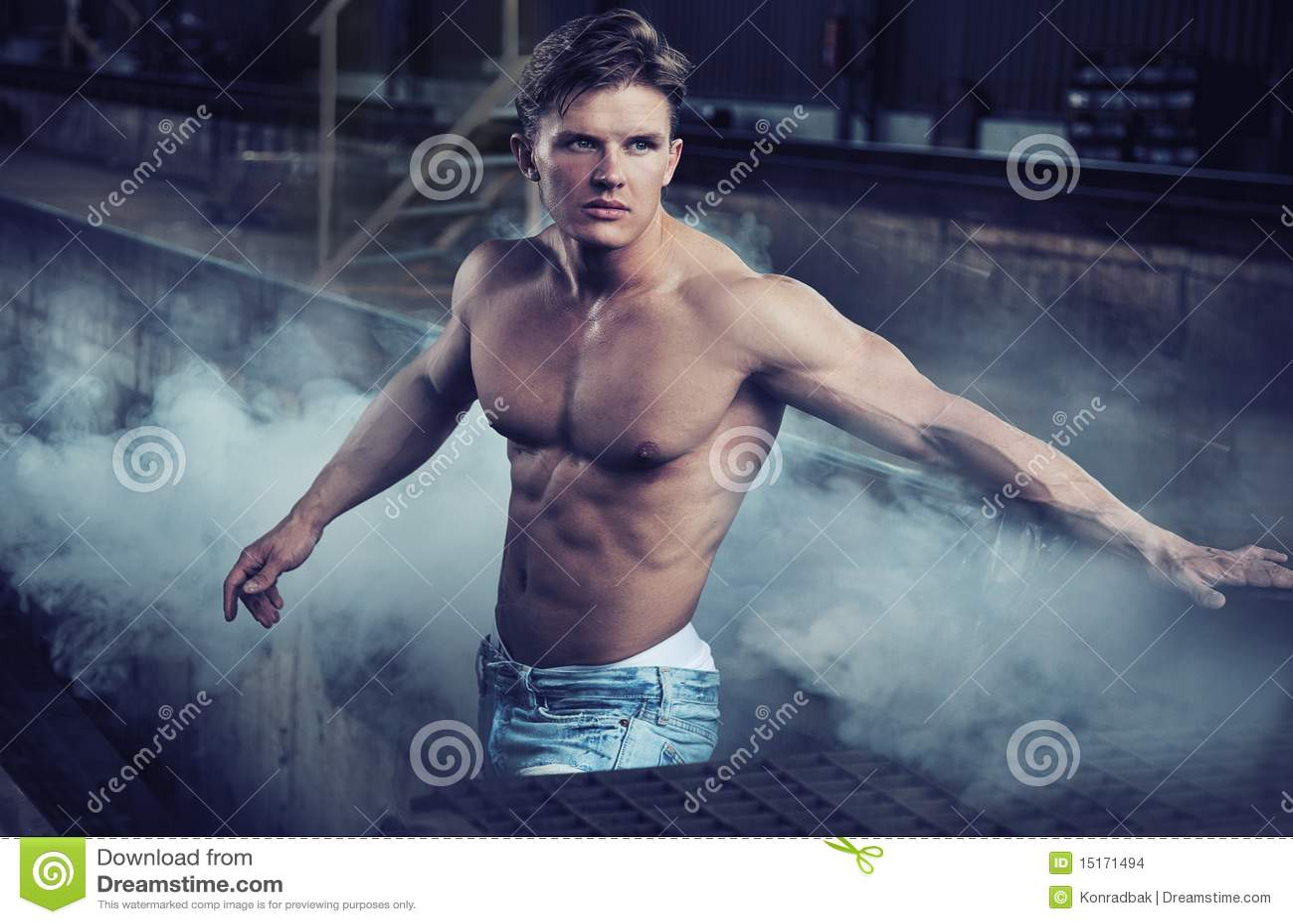 Calças de brim desgastando do bodybuilder considerável