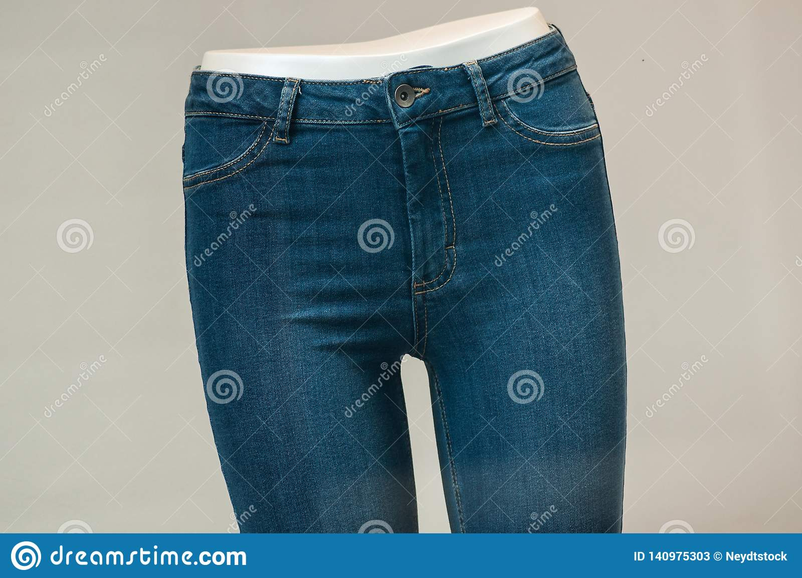 Calças de ganga elástica no manequim na sala de exposições da loja da forma das mulheres