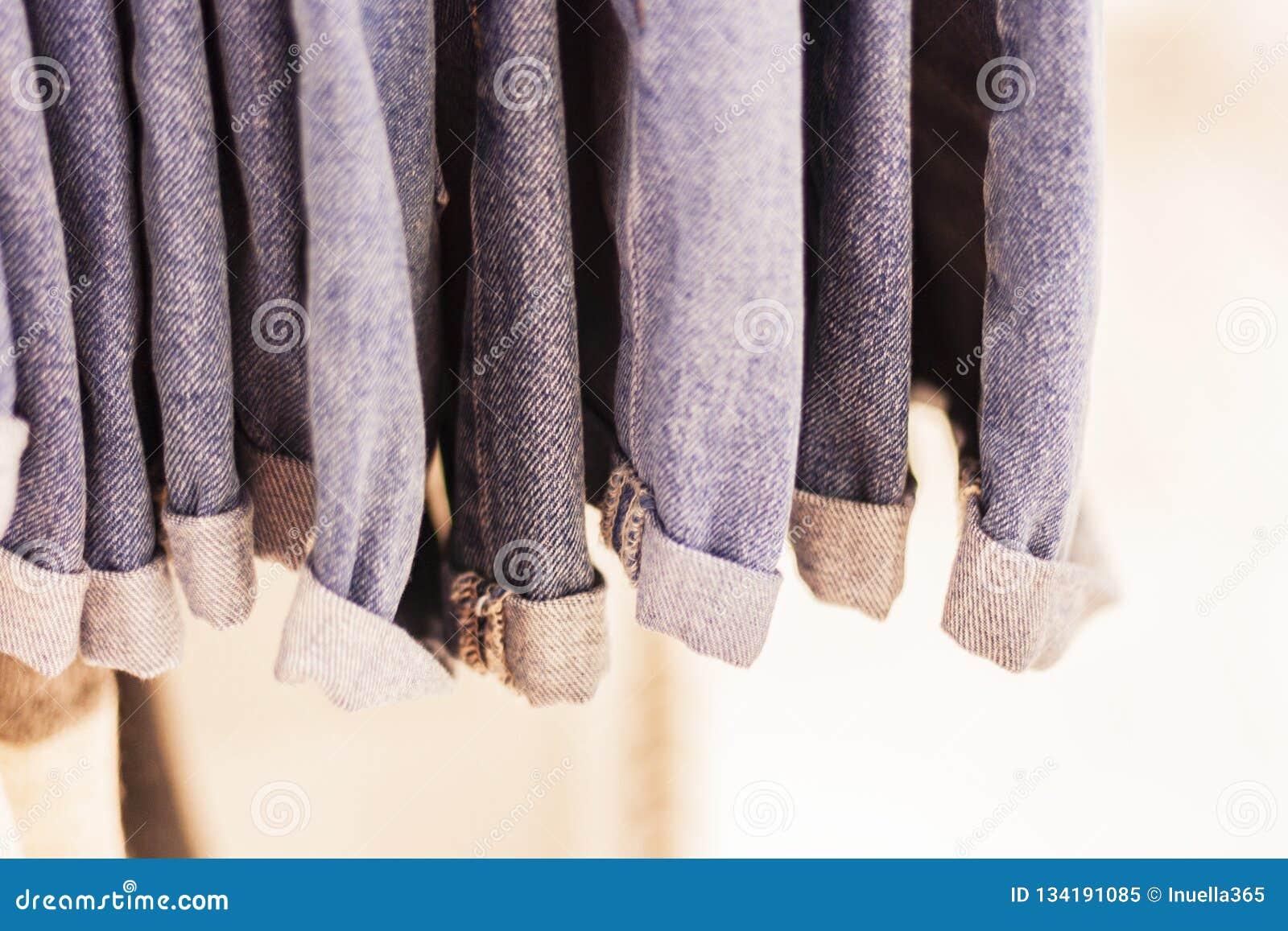 Calças de ganga no cair da loja em um gancho