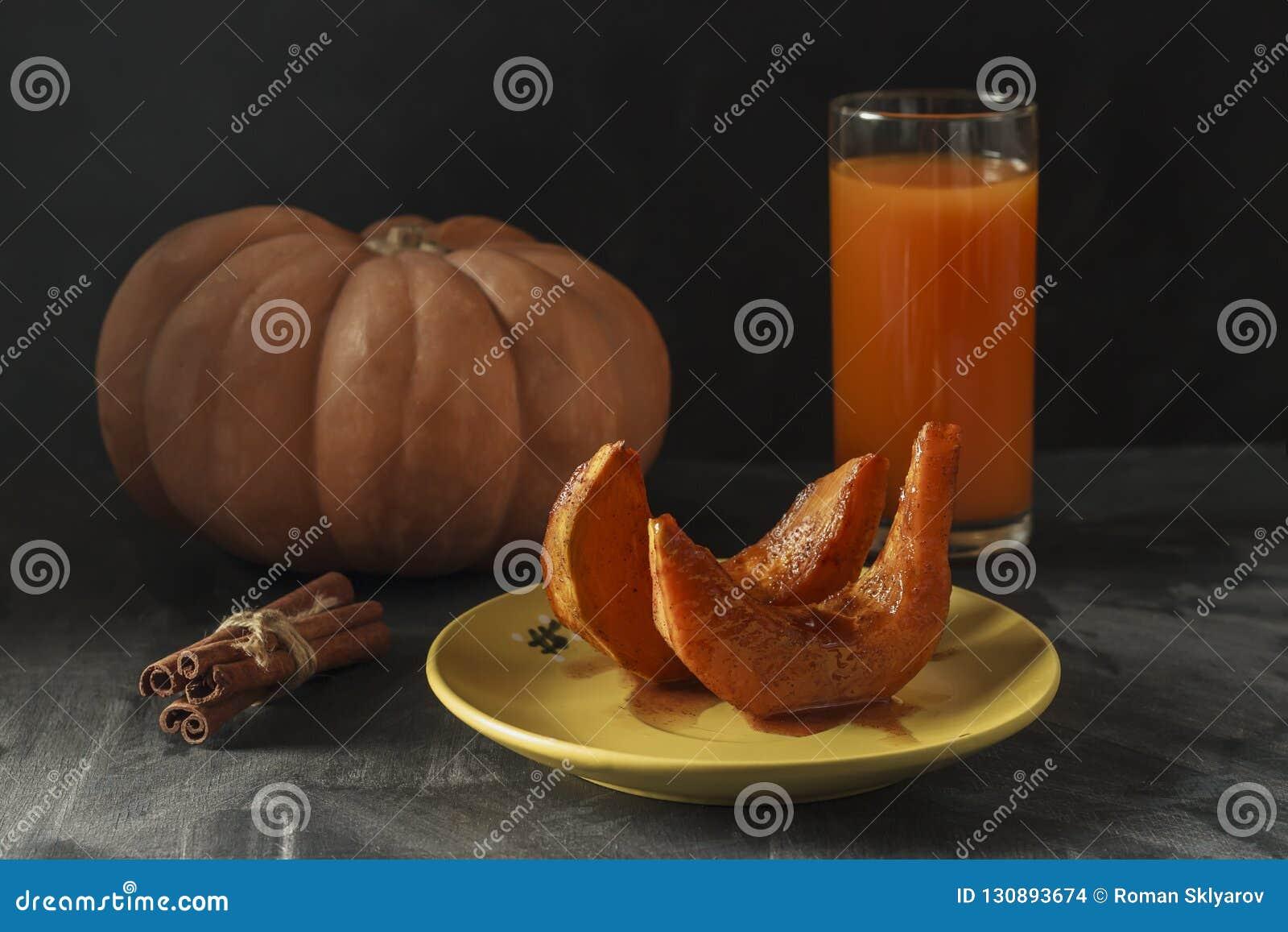 Calabaza cocida con los palillos de canela, la cuchara rústica y un vidrio de jugo