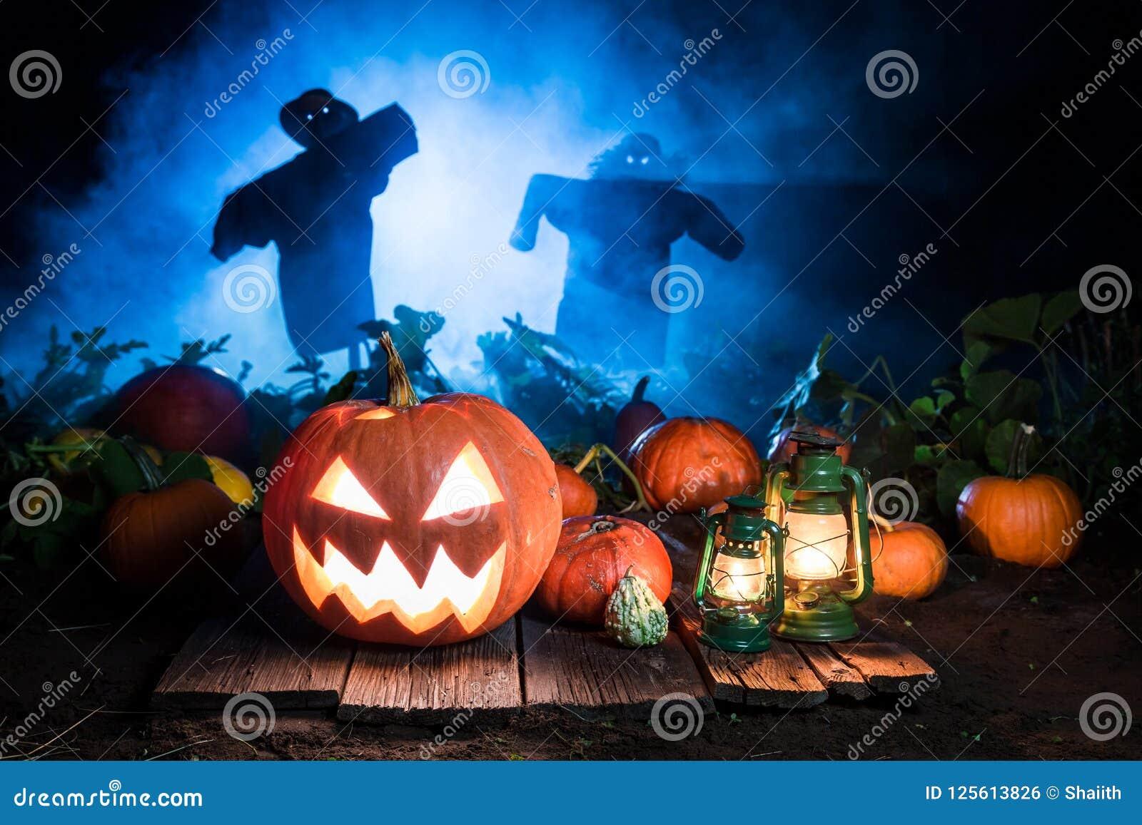 Calabaza de Halloween con los espantapájaros y la niebla azul