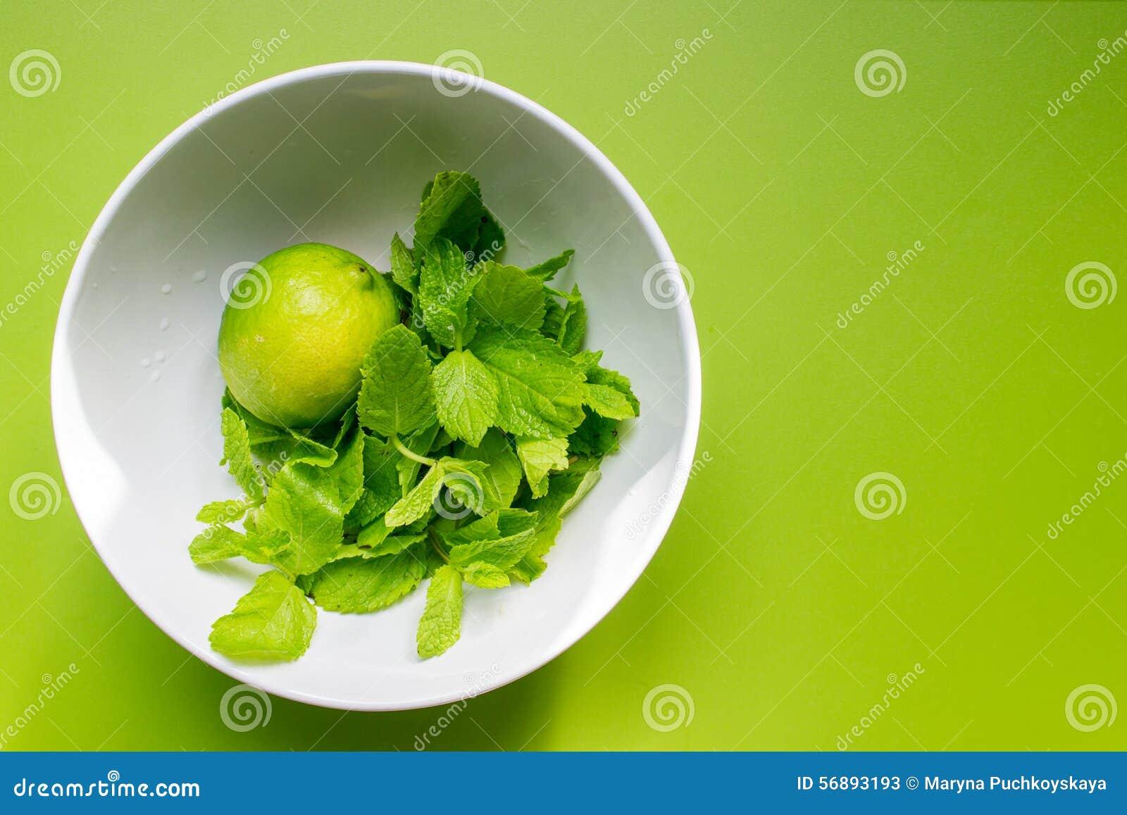 Calce fresca con la menta in tazza bianca su verde
