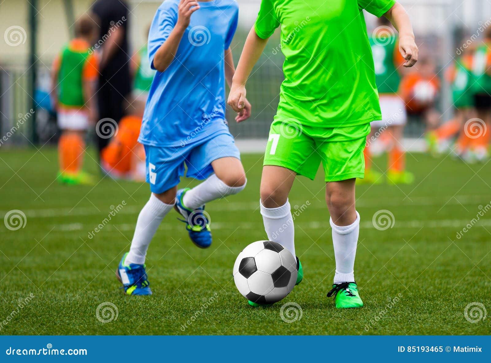 Calciatori della gioventù Ragazzi che danno dei calci alla palla di calcio sul campo