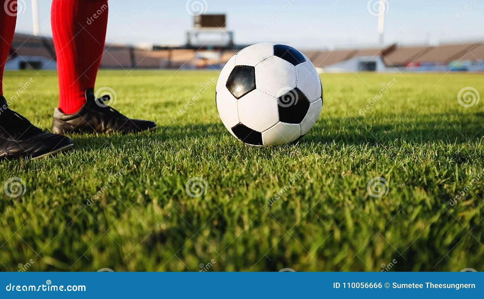 Calcio o giocatore di football americano che sta con la palla sul campo per Ki