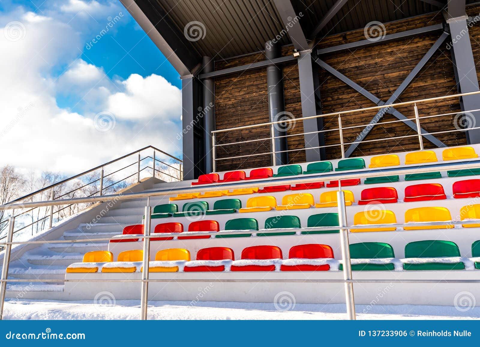 Calcio variopinto vuoto & x28; Soccer& x29; Sedili dello stadio nell inverno coperto in neve - Sunny Winter Day