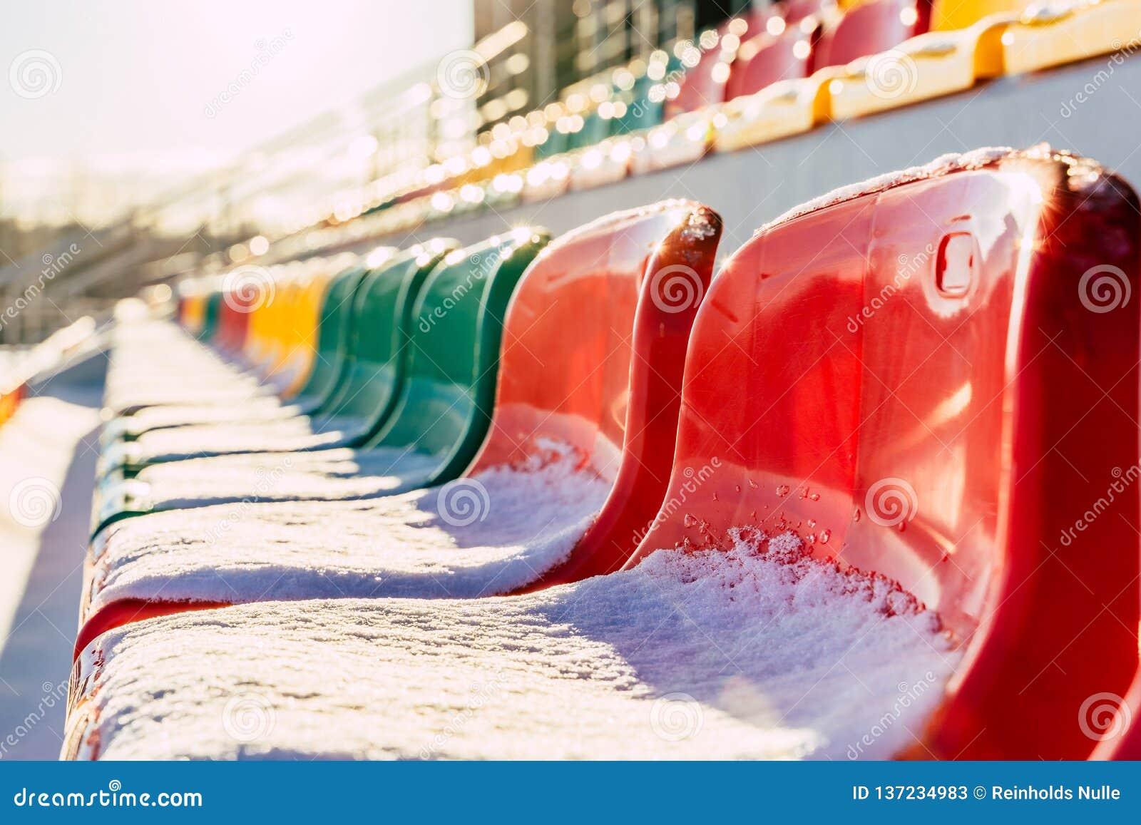 Calcio variopinto vuoto ( Soccer) Sedili dello stadio nell inverno coperto in neve - Sunny Winter Day con il chiarore di Sun
