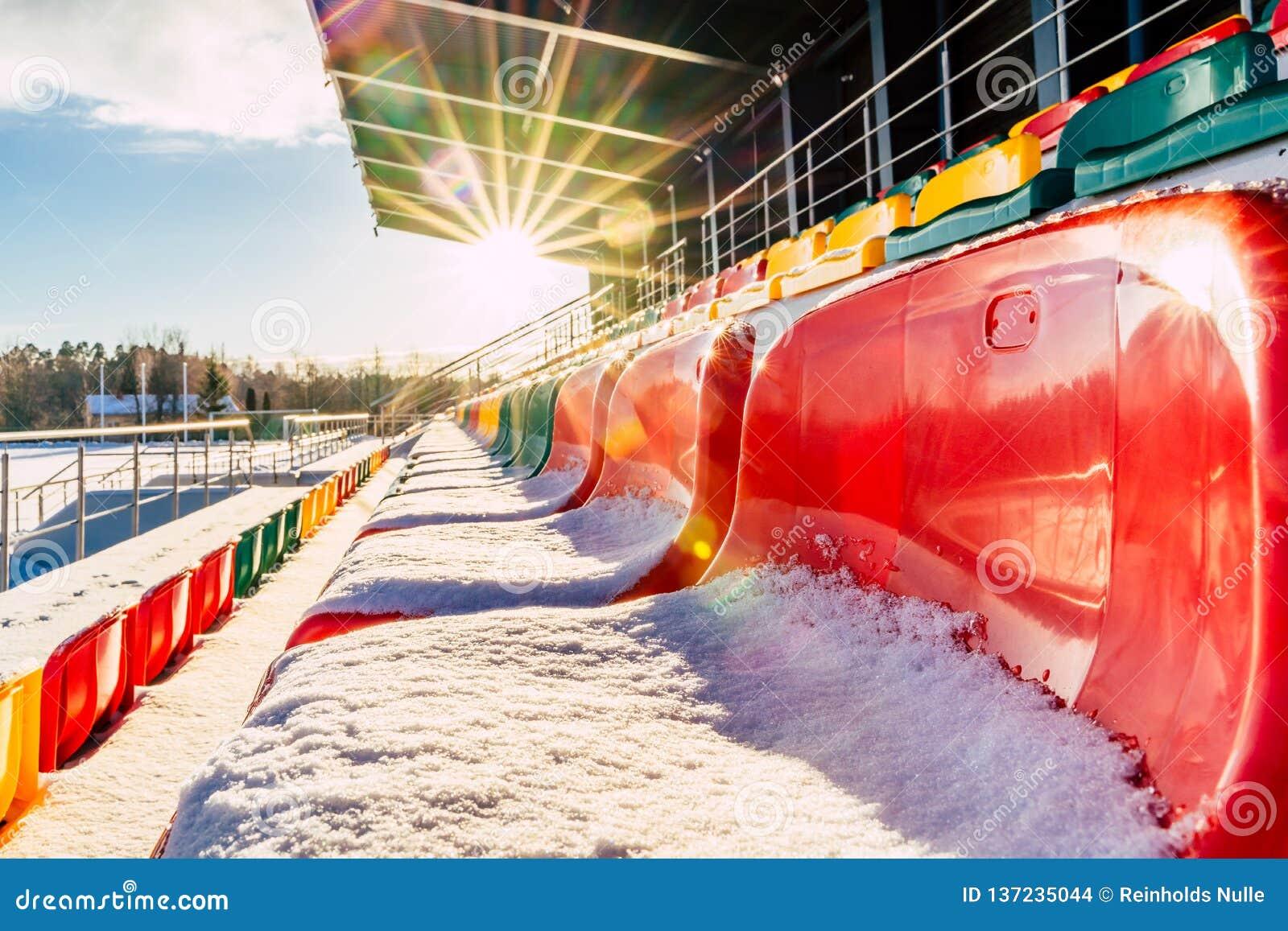 Calcio variopinto vuoto & x28; Soccer& x29; Sedili dello stadio nell inverno coperto in neve - Sunny Winter Day con il chiarore d