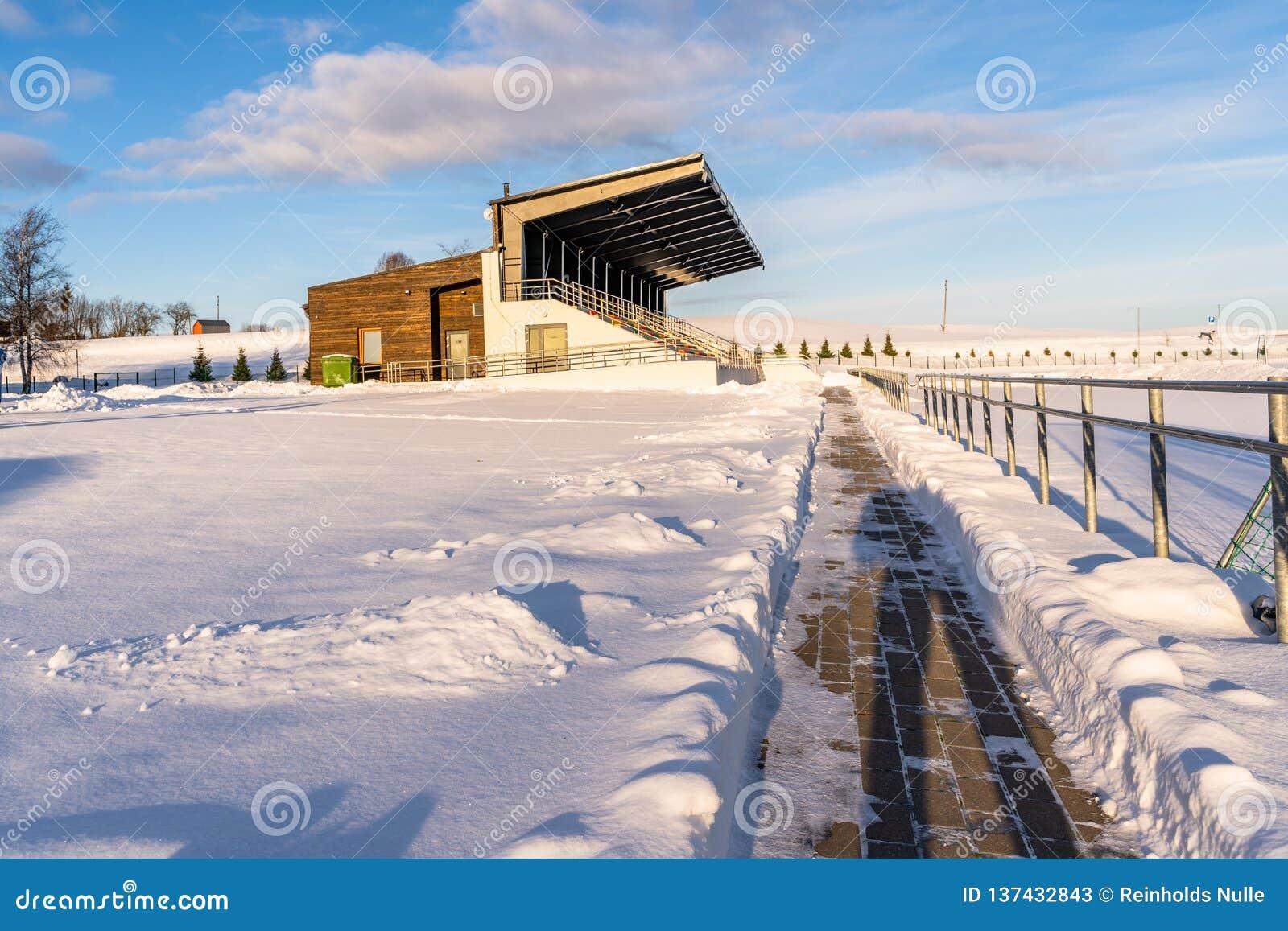 Calcio vuoto ( Soccer) Sedili dello stadio nell inverno coperto parzialmente in neve - Sunny Winter Day