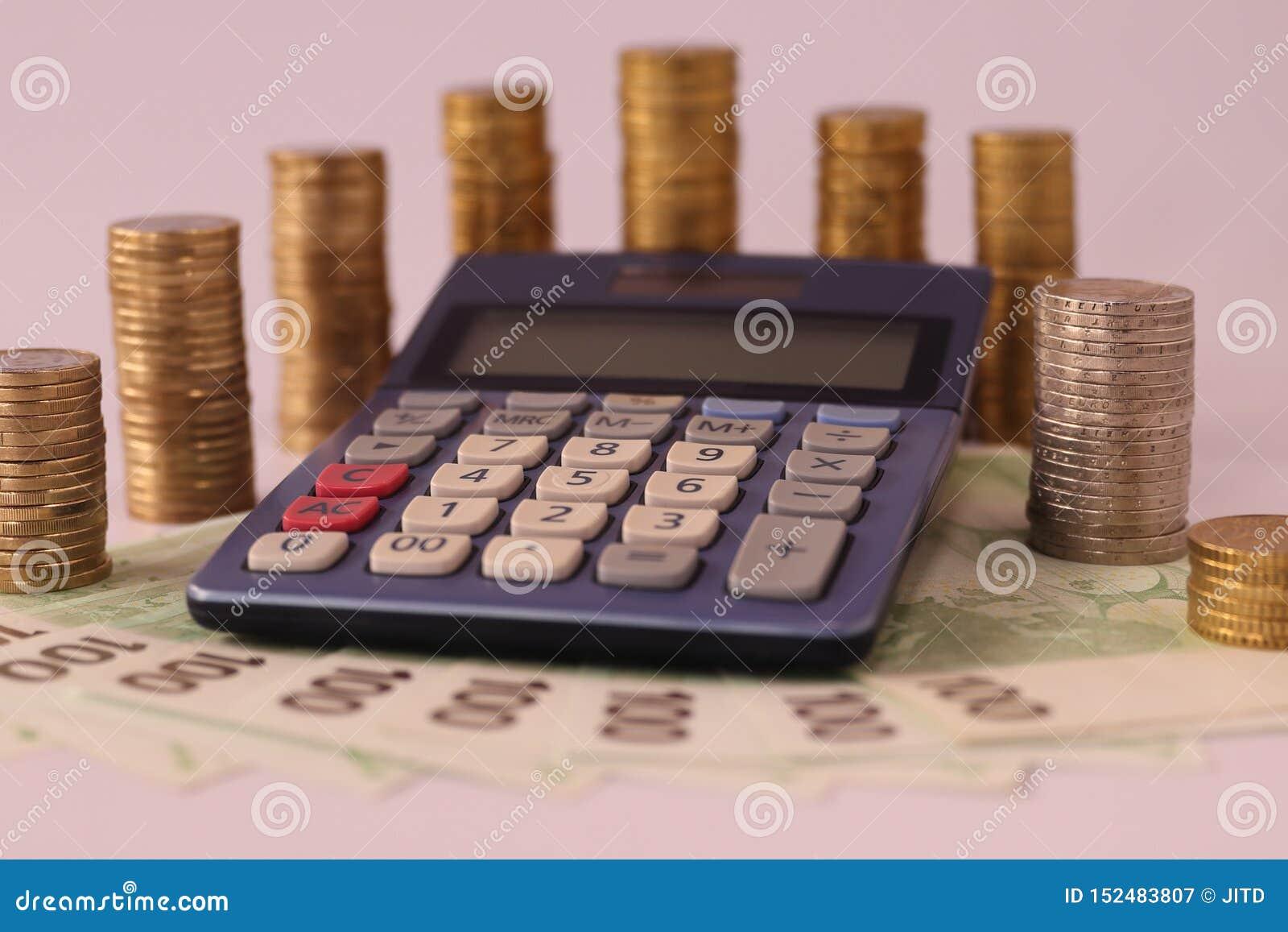 CALCOLATORE CIRCONDATO DALLE EURO MONETE IMPILATE SU UN EURO BIGLIETTO DI 100 EURO