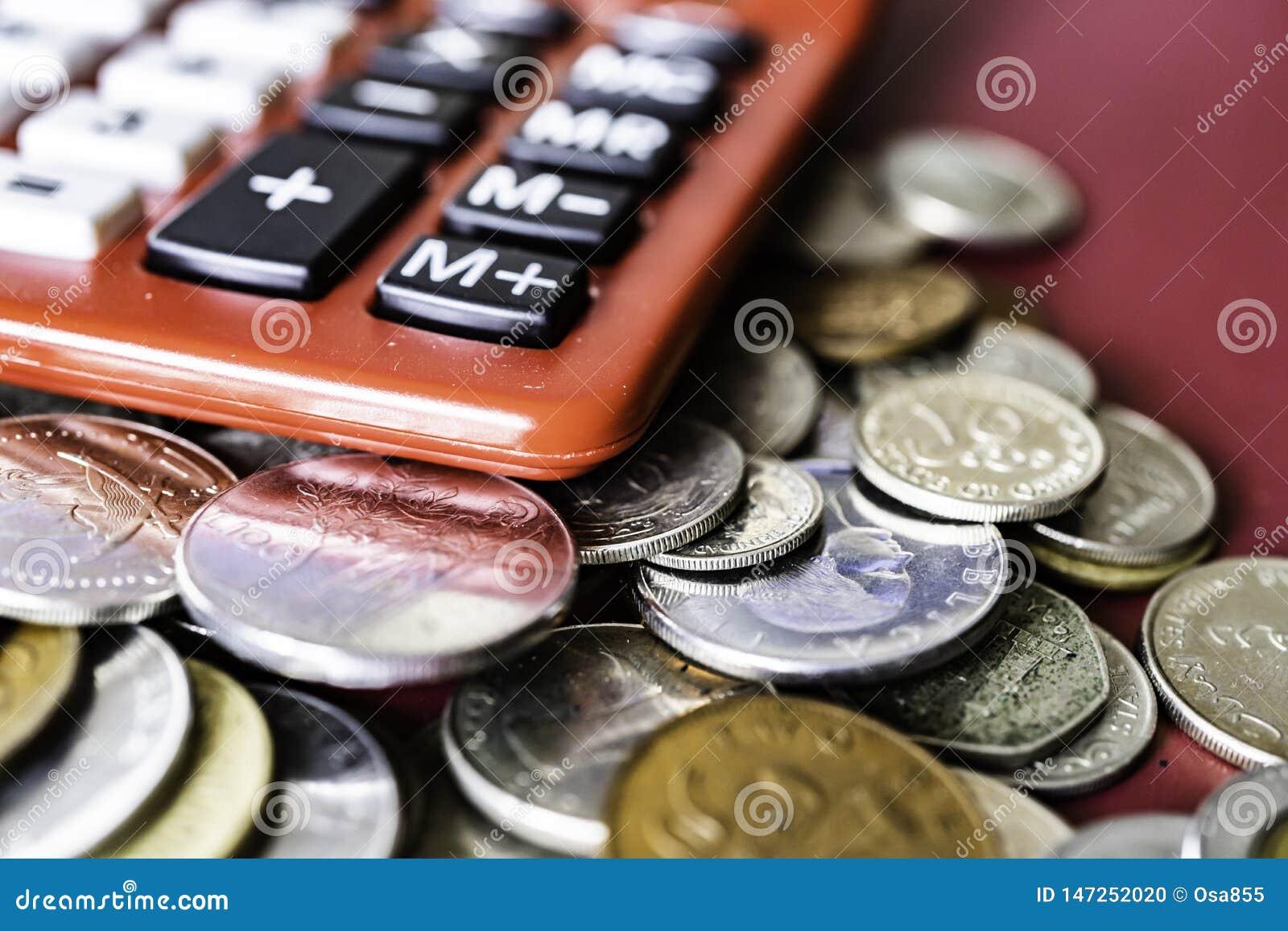 Calculadora vermelha do tampo da mesa com moedas de prata