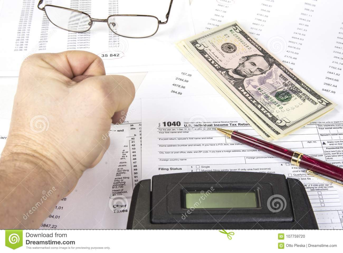 Calculating numbers for income tax return with pen, glasses and calculator.
