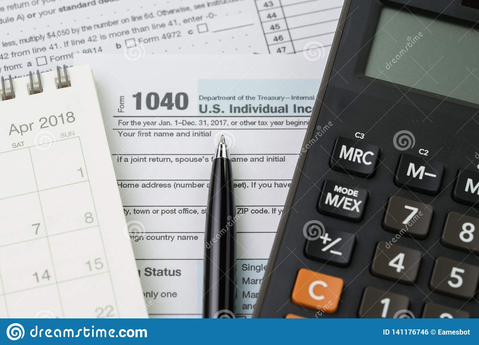 Calculator on calendar, pen and 1040 US individual income tax filling form, tax submission or revenue calculation concept