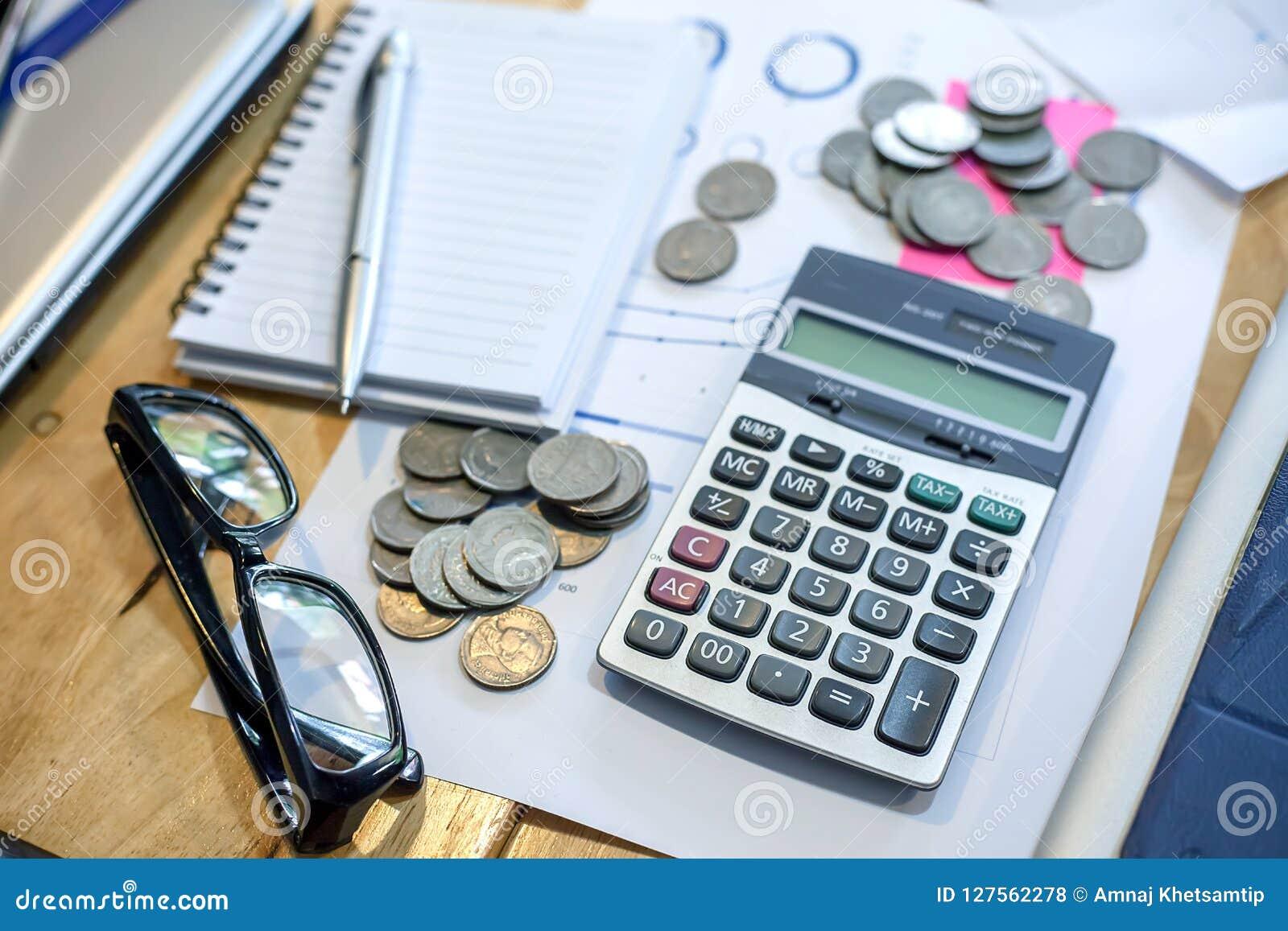 Calculator, notebook, pen, coins on his desk.