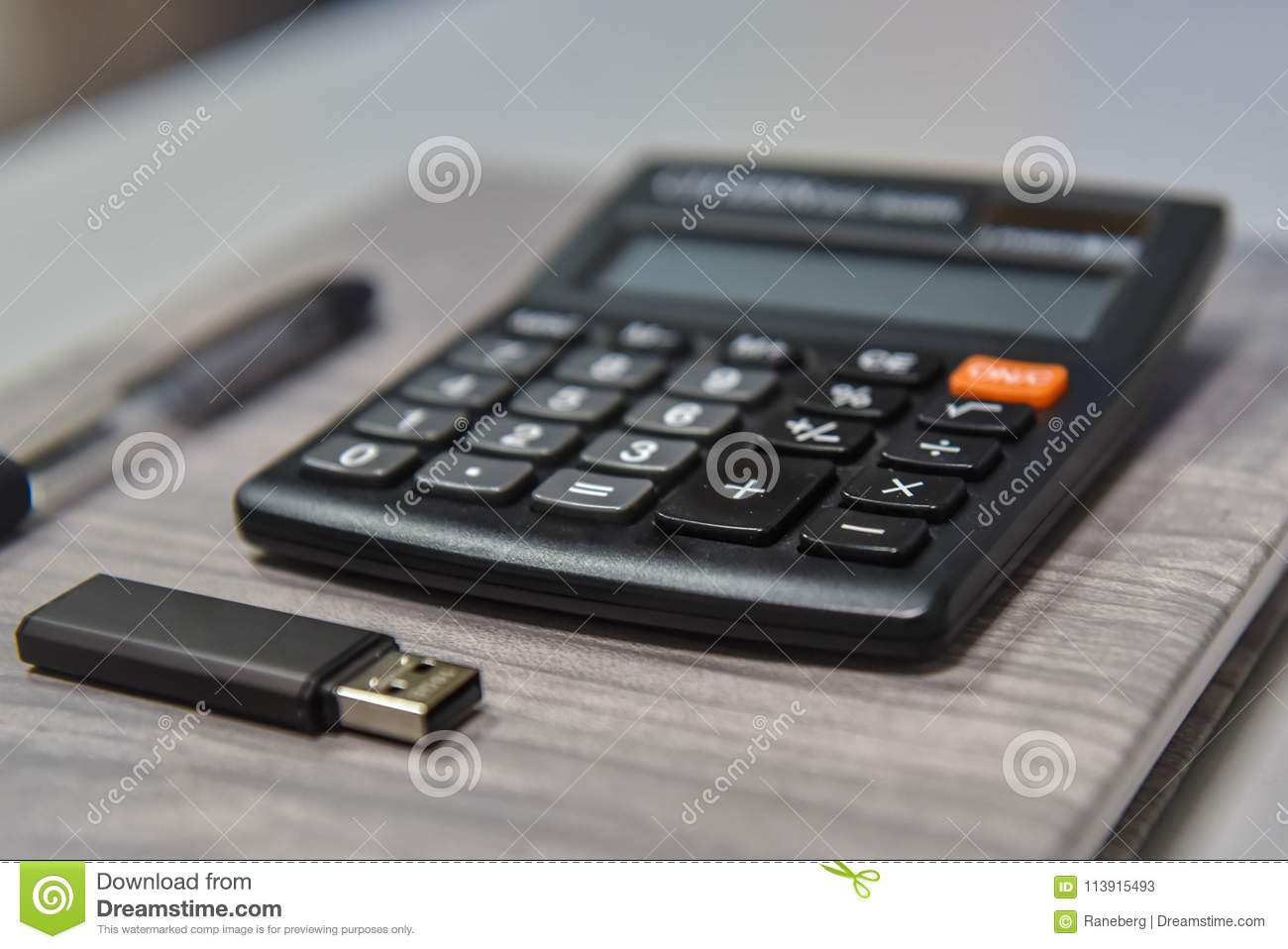 Calculator, pen and usb stick in the office