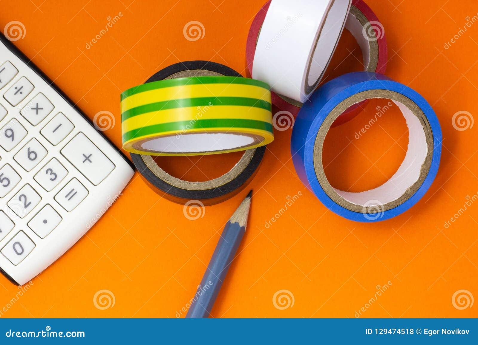Calculatrice, bande d isolation et crayon sur un fond orange