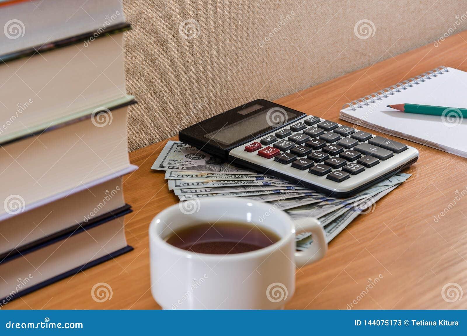 Calculatrice, dollars, bloc-notes et livres sur la table