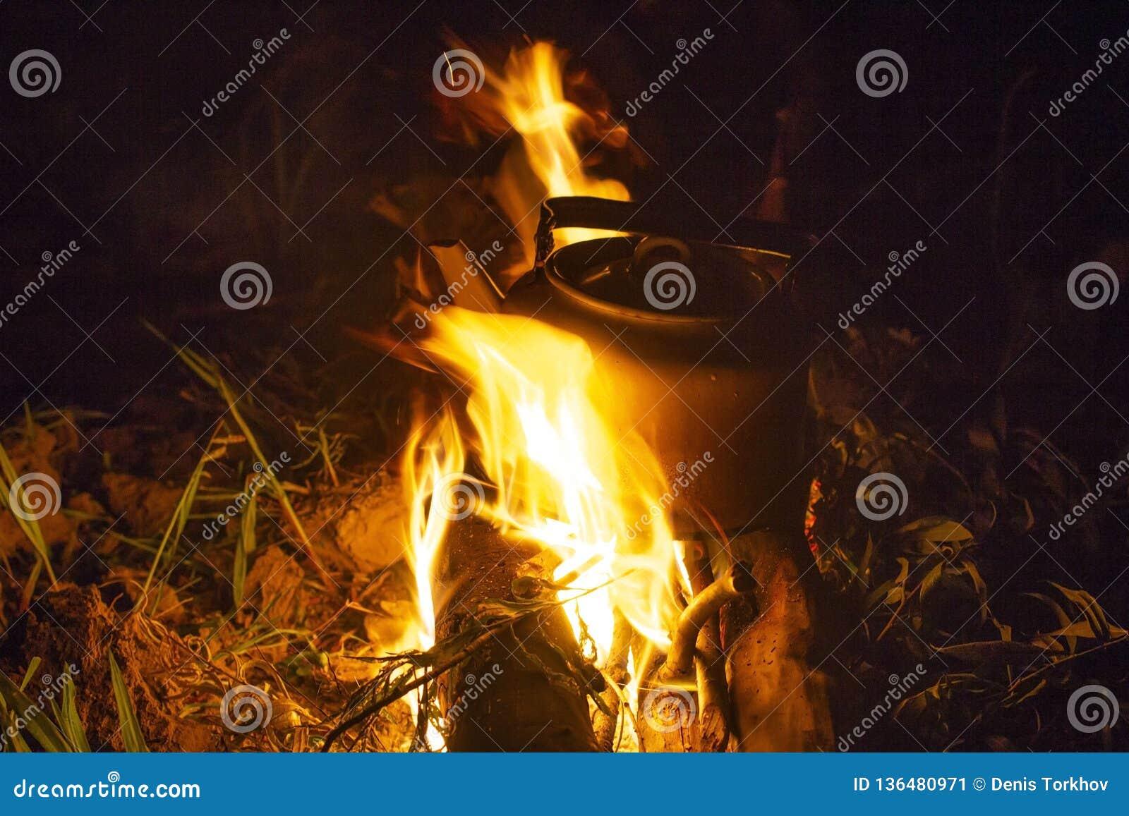 Caldera que acampa en el fuego en una caldera al aire libre del sitio para acampar para el café mientras que campin