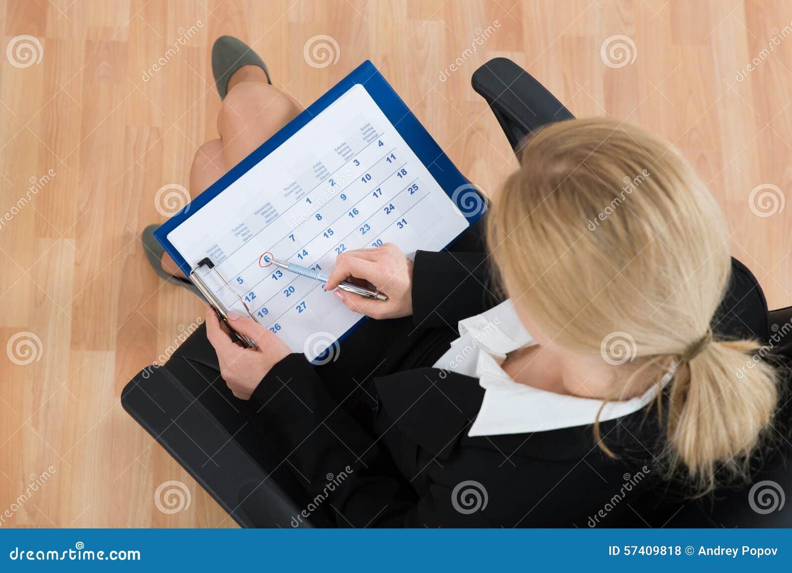 Calendário de Marking Date On da mulher de negócios