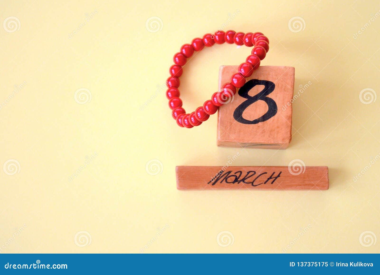 Calendário perpétuo de madeira do 8 de março e um bracelete coral vermelho brilhante em um fundo amarelo com espaço da cópia