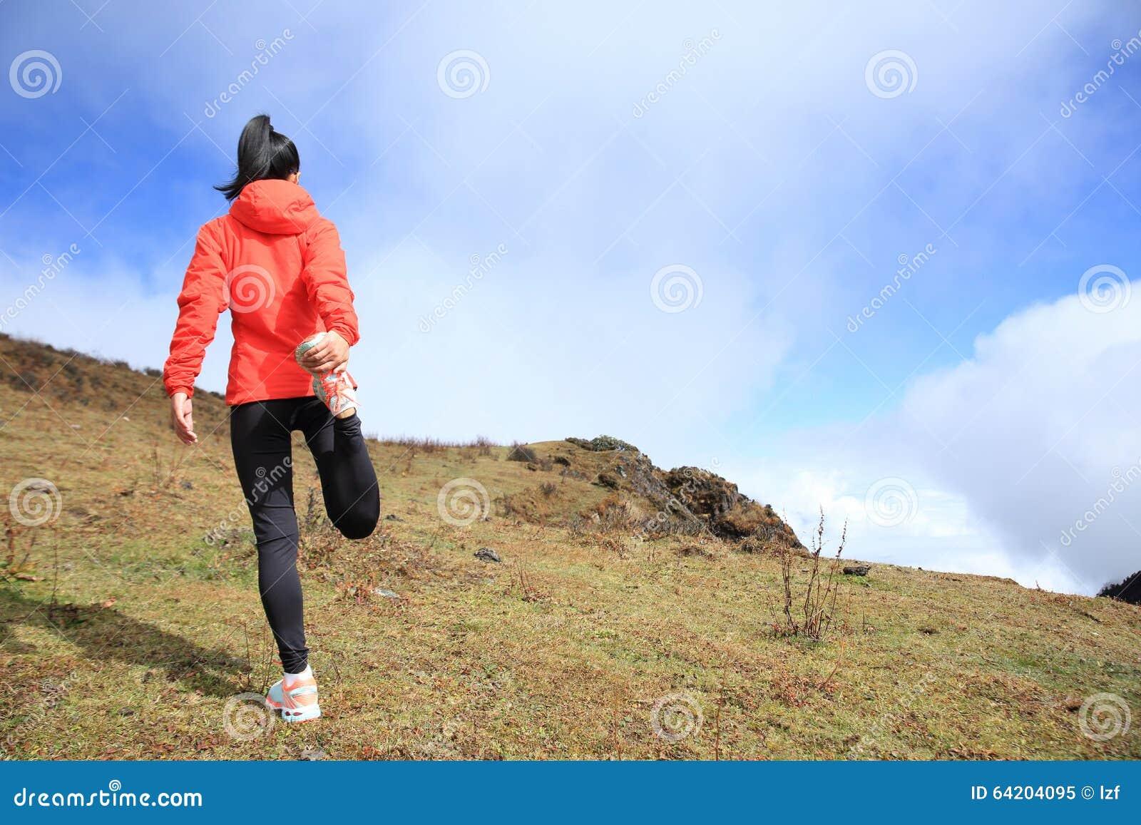 Calentamiento del corredor del rastro de la mujer en pico de montaña