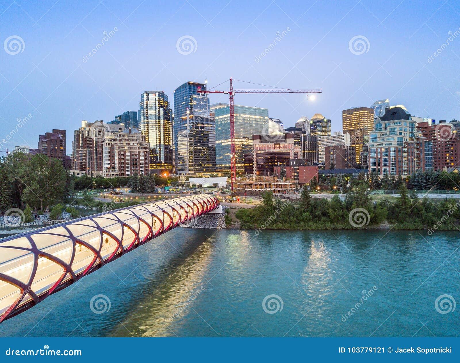 Calgary céntrica con el puente iluminated de la paz, Alberta, Canadá