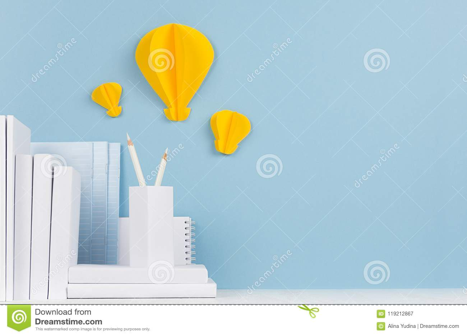 Calibre d école - livres blancs, papeterie, origami jaune de papier décoratif d ampoules sur le bureau blanc et fond bleu mou